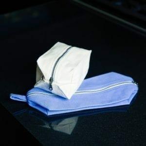 White dopp bag and blue folded dopp bag
