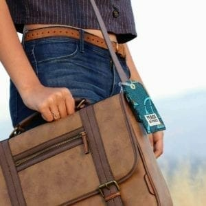 brown satchel with blue luggage tag