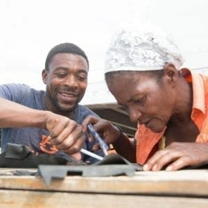 man helping woman cut rubber