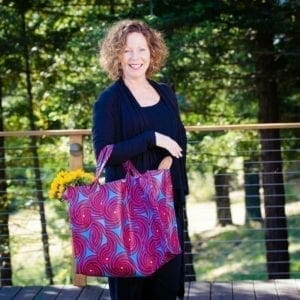 Woman holding big blue and pink tote bag