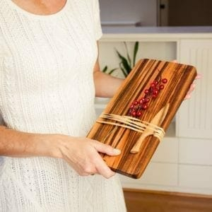 Woman holding cutting board with knife