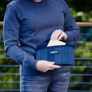 Woman in blue pulling item out of pouch