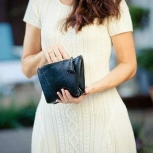 Woman in white dress holding black clutch