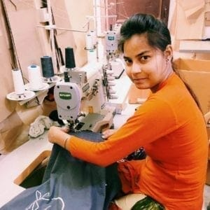 woman at sew mach in orange sweater